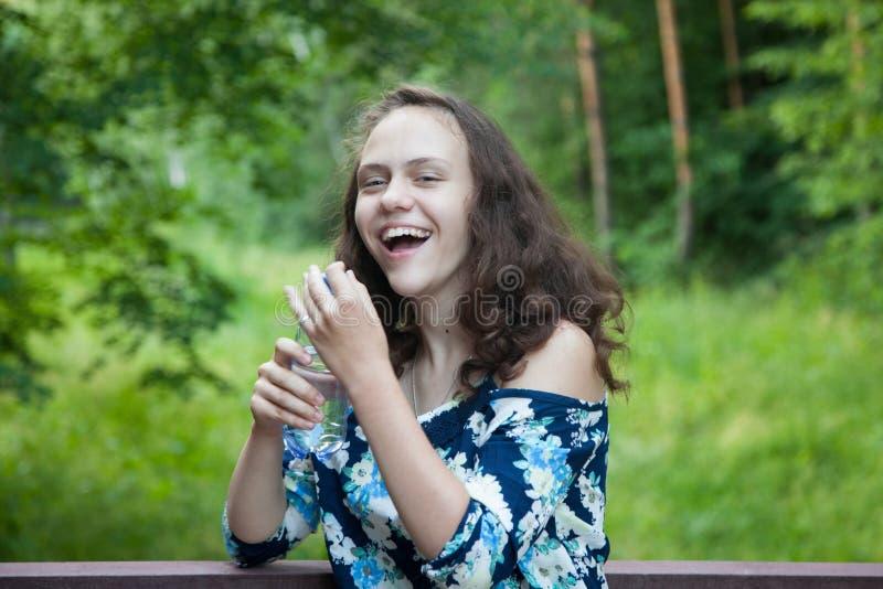Lachend, vrolijke gelukkige tiener in aard, in de handen van schoon drinkwater in een fles royalty-vrije stock foto