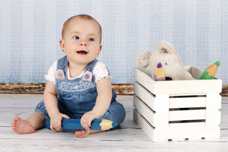 Lachend weinig babymeisje met groot potlood en pluchespeelgoed stock fotografie