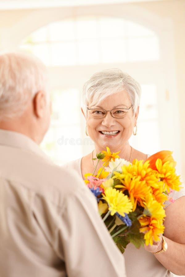 Lachende ältere Frau, die Blumenstrauß erhält lizenzfreie stockfotografie