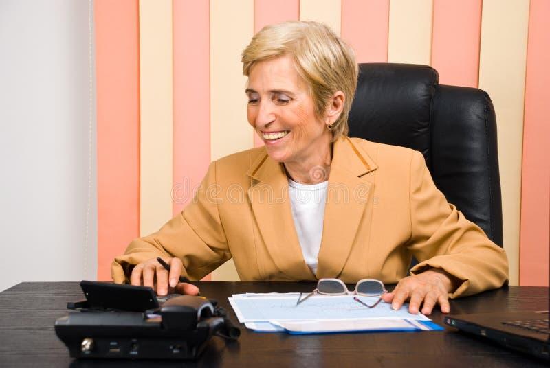 Lachende ältere Geschäftsfrau, die Rechner verwendet stockfotografie