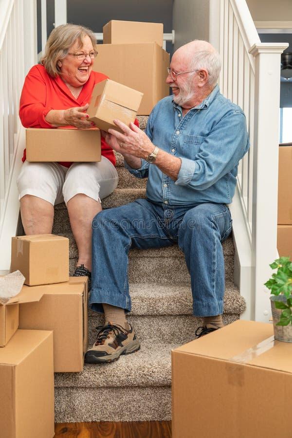 Lachende ältere Paare, die auf der Treppe umgeben durch die Bewegung von Kästen stillstehen lizenzfreies stockfoto