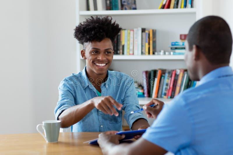 Lachende Afrikaanse Amerikaanse leerling die contract ondertekenen stock afbeelding