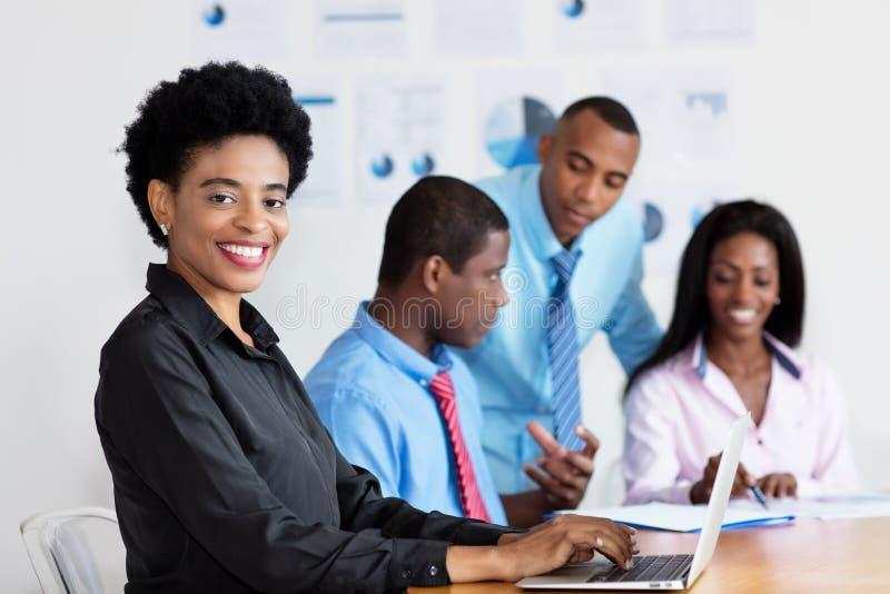 Lachende Afrikaanse Amerikaanse onderneemster aan het werk op kantoor royalty-vrije stock foto