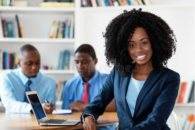 Lachende Afrikaanse Afrikaanse onderneemster met commercieel team royalty-vrije stock foto's