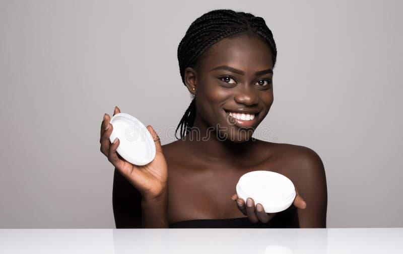 Lachende afrikanische Frau mit Feuchtigkeitscreme auf ihrem Gesicht Porträt der Afroamerikanerfrau mit makelloser Haut auf Weiß lizenzfreie stockfotografie