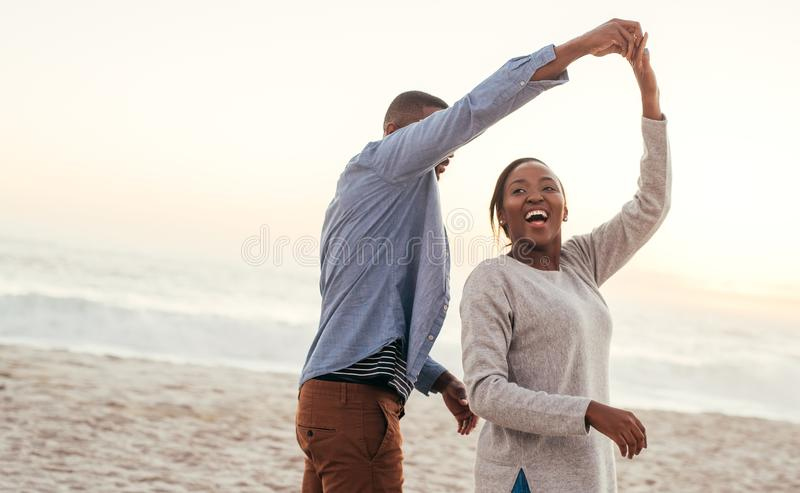 Lachende afrikanische Paare, die zusammen auf einen Strand bei Sonnenuntergang tanzen lizenzfreie stockfotos