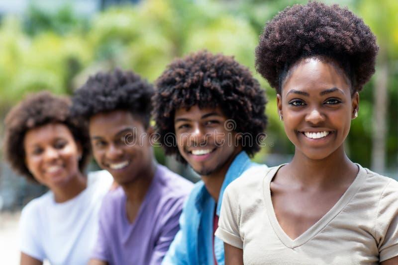 Lachende Afroamerikanerfrau mit Gruppe jungen Erwachsenen in der Linie lizenzfreies stockfoto