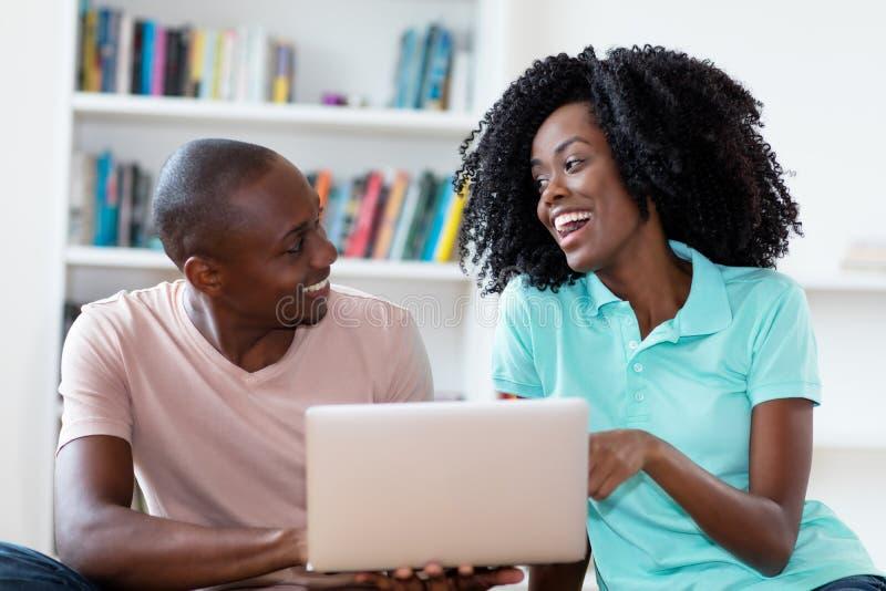 Lachende Afroamerikanerpaare mit Computer lizenzfreie stockbilder