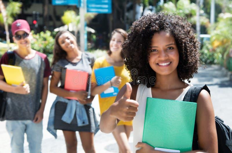 Lachende Afroamerikanerstudentin, die Daumen mit grou zeigt lizenzfreie stockfotos