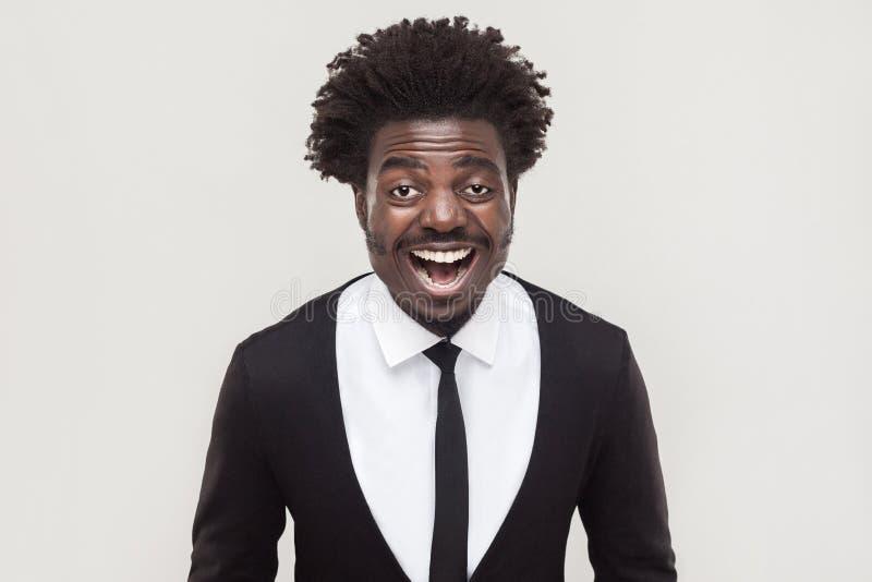 Lachende afrozakenman die camera en het toothy glimlachen bekijken stock afbeeldingen