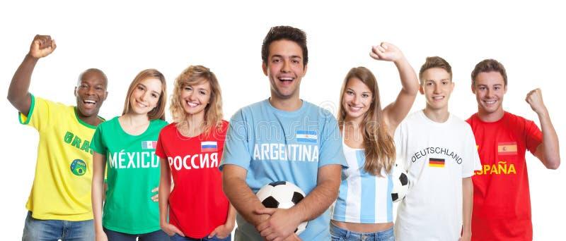 Lachende Argentijnse voetbalverdediger met bal en ventilators van ot stock afbeelding