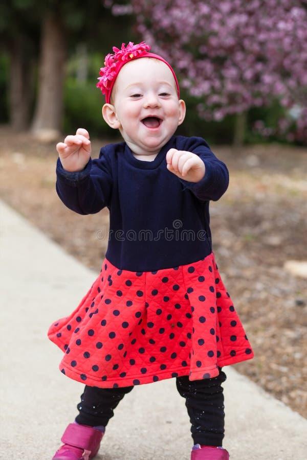 Lachende baby die eerste maatregelen treffen stock fotografie
