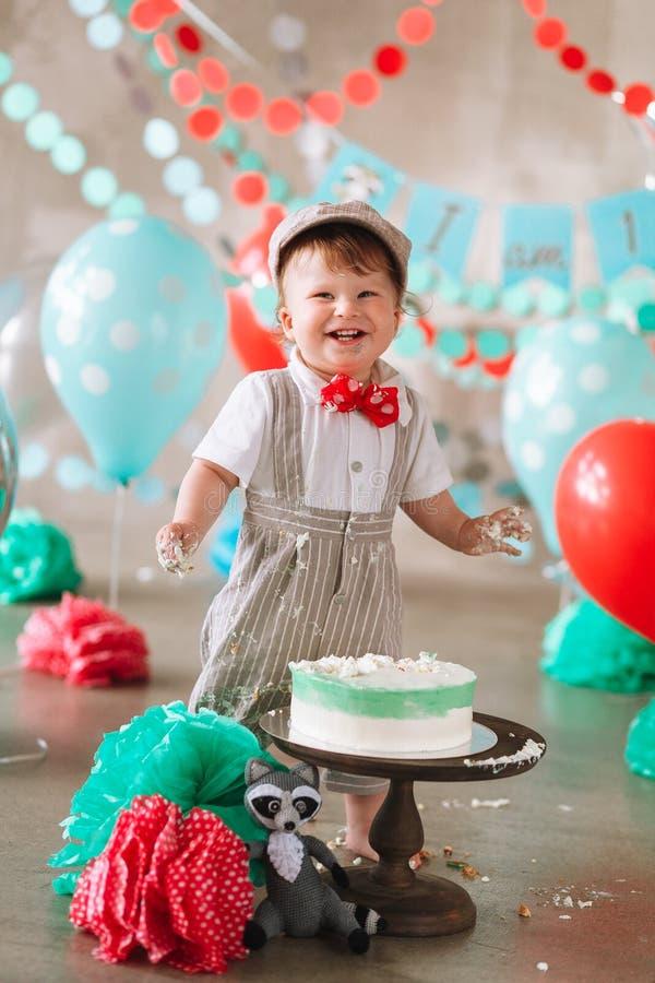 Lachende babyjongen in zijn eerste ineenstorting van de verjaardagscake Slordige vuile handen en gelukkig gezicht royalty-vrije stock fotografie