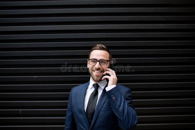 Lachende bedrijfsmens met smartphone stock fotografie
