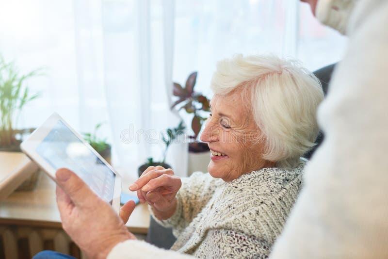 Lachende Bejaarde Dame Using Tablet royalty-vrije stock afbeelding