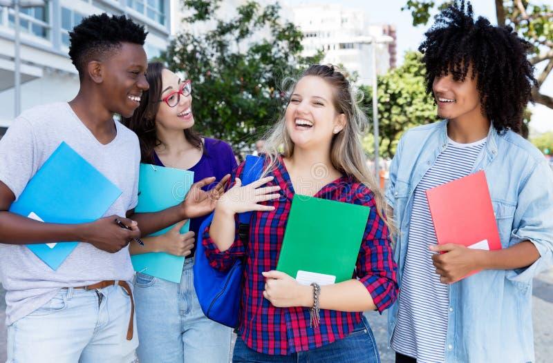Lachende blonde vrouwelijke student met groep internternationalstudenten stock foto's
