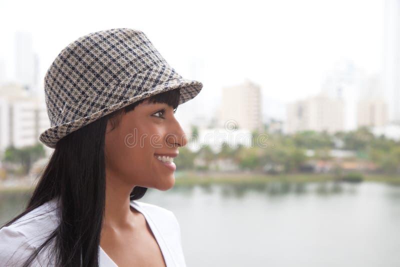 Lachende brasilianische Frau mit dem Hut, der seitlich schaut stockfotografie