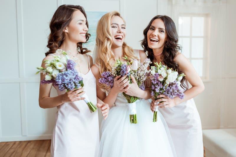Lachende Braut mit Brautjungfern lizenzfreie stockbilder