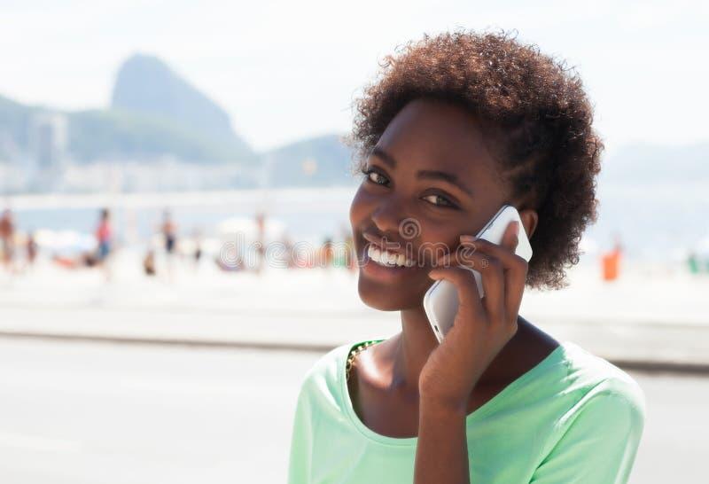 Lachende Braziliaanse vrouw in Rio de Janeiro bij telefoon stock afbeelding