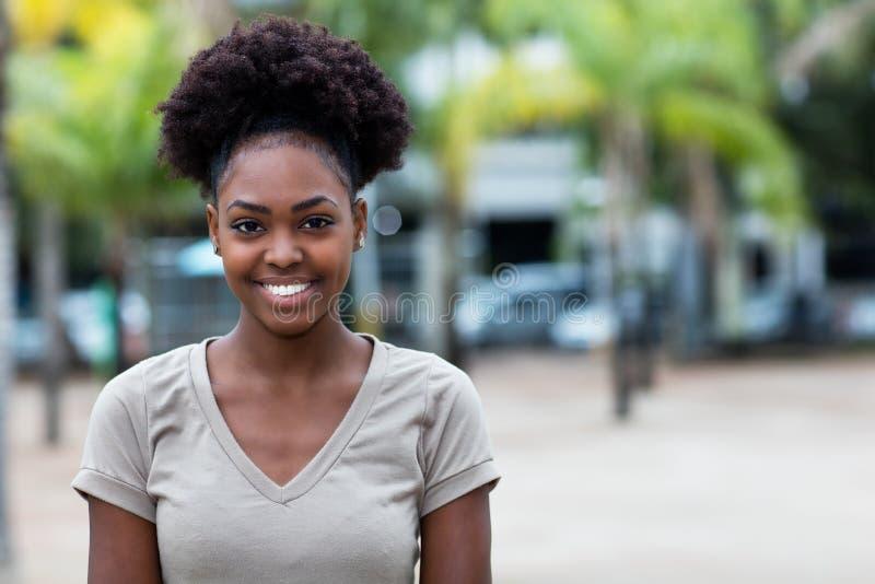 Lachende Caraïbische vrouw met afrohaar royalty-vrije stock afbeelding