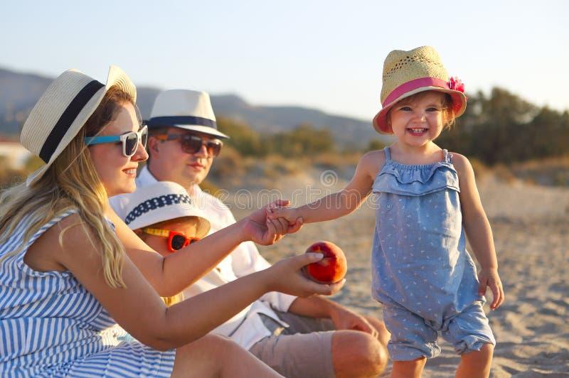 Lachende familie met vader, moeder die, dochters picknick heeft bij het strand stock afbeeldingen
