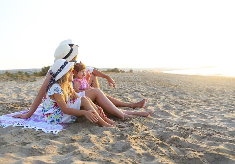Lachende familie met vader, moeder die, dochters picknick heeft bij het strand royalty-vrije stock foto's