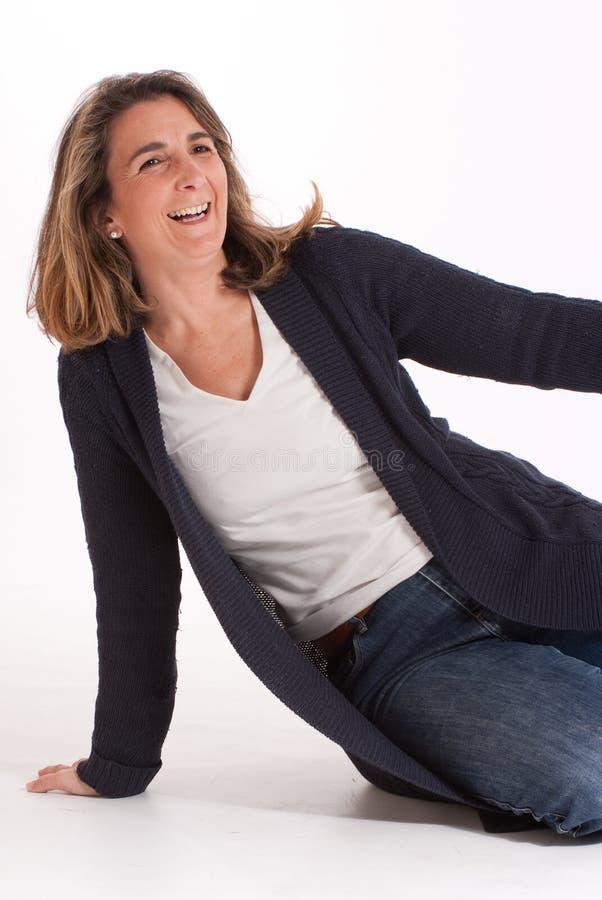 Lachende Frau auf dem Boden stockfotografie