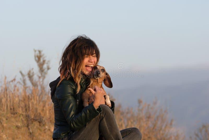 Lachende Frau beim Halten des Dachshundhundes stockfotografie