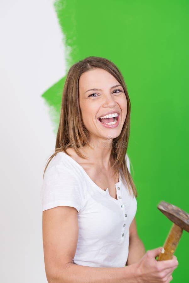 Lachende Frau, die einen Hammer hält stockfoto