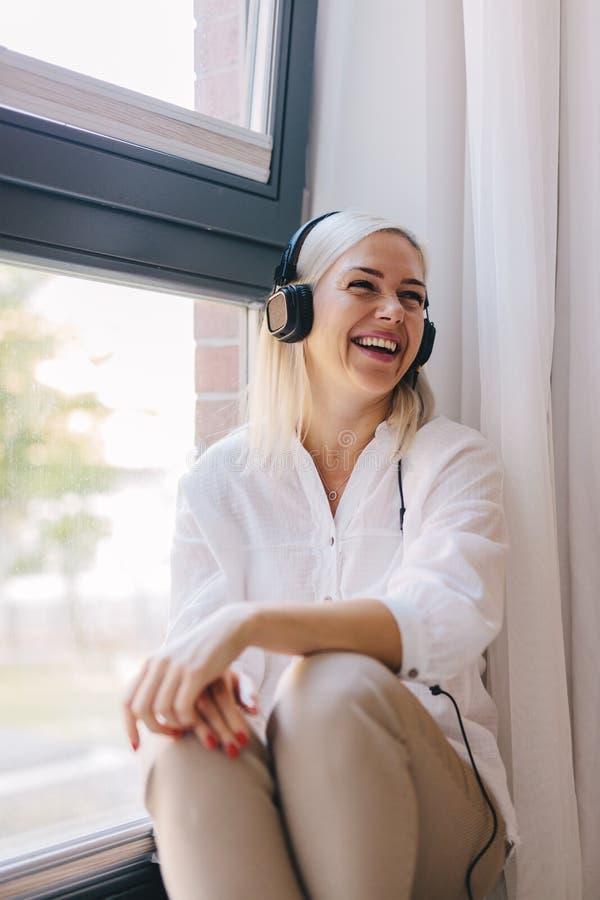 Lachende Frau, die Musik auf Kopfhörern hört stockfotos