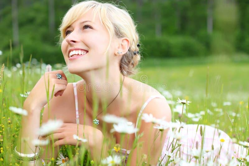 Lachende Frau, die unter weißen Gänseblümchen liegt lizenzfreie stockfotos