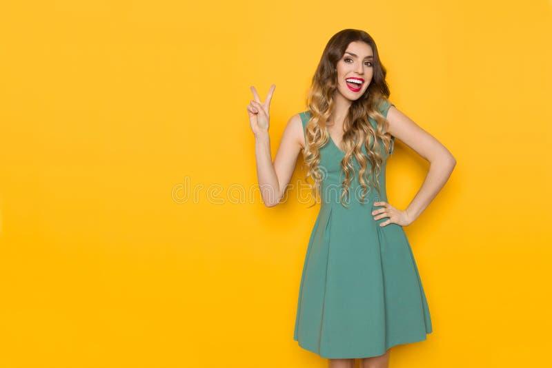 Lachende Frau im grünen Mini Dress Is Showing Peace-Handzeichen lizenzfreie stockfotografie