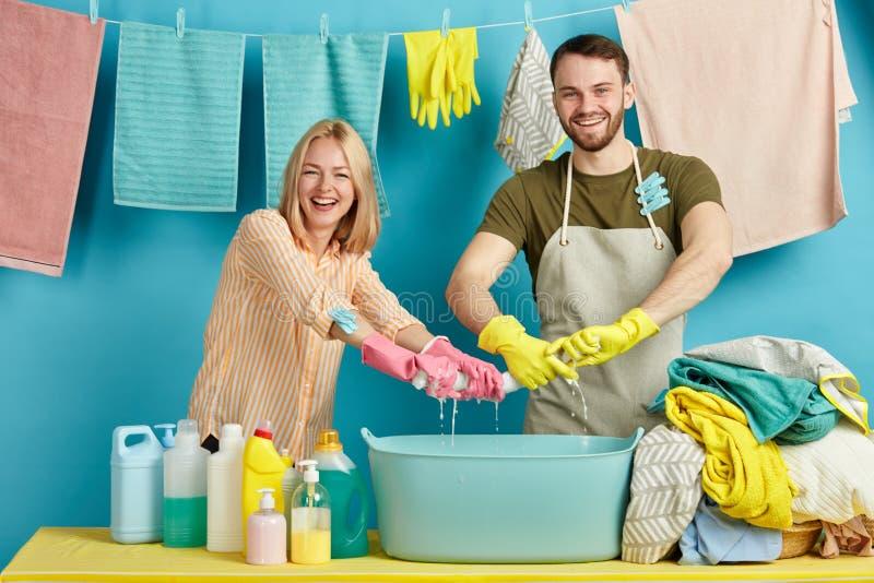 Lachende Frau und Mann beim Setzen der zufälligen Kleidung, Tuch ausdehnend lizenzfreie stockfotografie