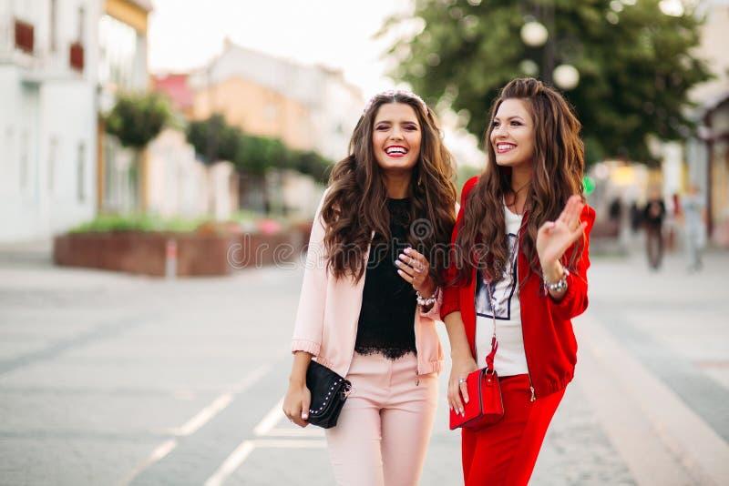 Lachende Frauen in den schicken Klagen des Sports und Handtaschen in der Straße lizenzfreies stockfoto