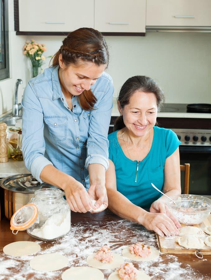 Lachende Frauen, die Torten oder Fleischmehlklöße machen stockbilder