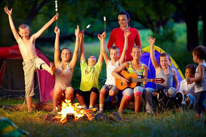 Lachende Freunde, die Spaß um Lagerfeuer haben stockbilder