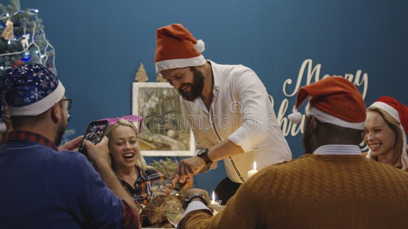 Lachende Freunde, die Truthahn am Weihnachtsessen gebraten werden stockfotos