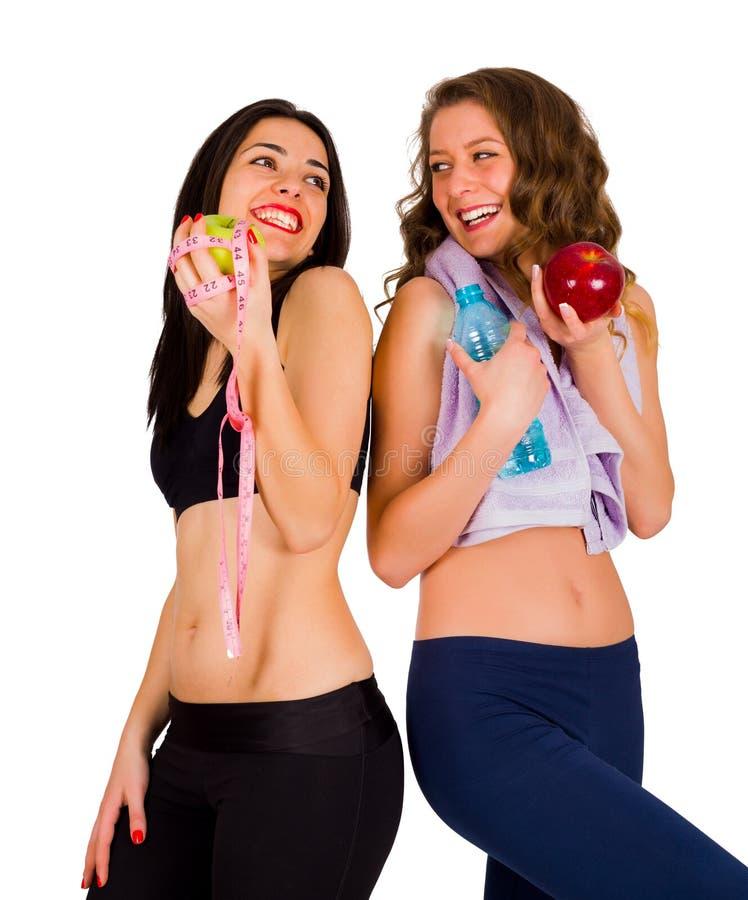 Lachende geeignete Frauen, die gesundes Lebensmittel essen stockfoto