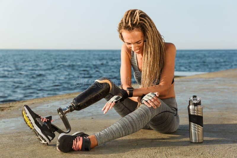 Lachende gehandicapte atletenvrouw met prothetisch been stock afbeeldingen