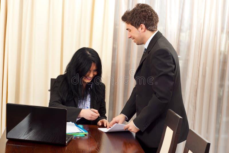 Lachende Geschäftsleute, die Papiere unterzeichnen lizenzfreie stockfotos