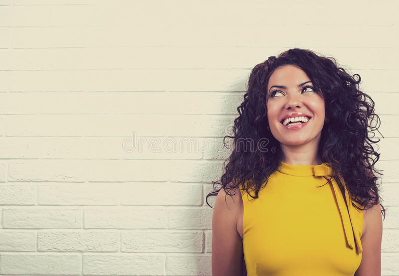 Lachende glückliche Frau, lokalisiert auf Backsteinmauerhintergrund stockfotos