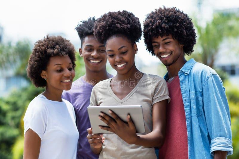 Lachende groep Afrikaanse Amerikaanse studenten met digitale tablet stock foto