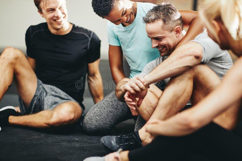 Lachende groep diverse vrienden die samen in een gymnastiek zitten royalty-vrije stock afbeeldingen