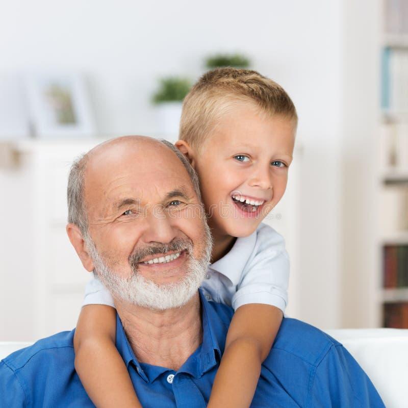 Lachende grootvader met zijn kleinzoon stock foto