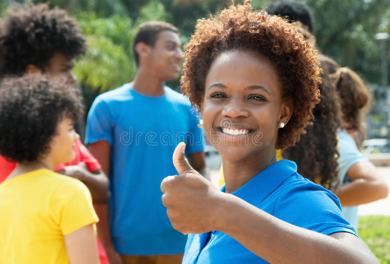 Lachende jonge Afrikaanse Amerikaanse vrouw die duim met groep o tonen stock afbeeldingen