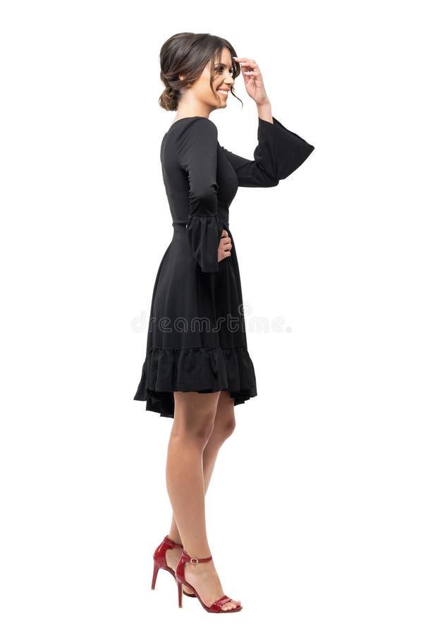 Lachende jonge Latijnse vrouw die in zwarte kleding weg kijken Zachte nadruk royalty-vrije stock afbeeldingen