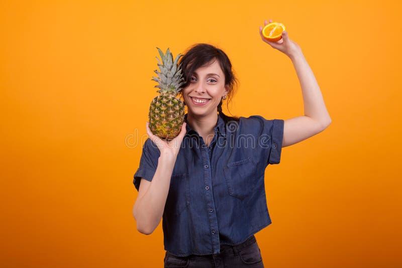 Lachende jonge mooie vrouw met tropische vruchten in studio over gele achtergrond royalty-vrije stock fotografie