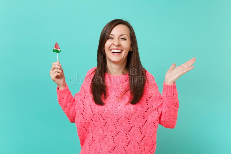 Lachende jonge vrouw in gebreide roze die sweater het uitspreiden handen en het houden van watermeloenlolly op blauw turkoois wor stock foto's