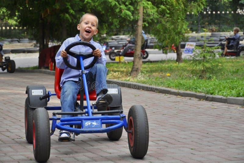 Lachende jongen in een pedaalkar, die pret heeft stock foto's