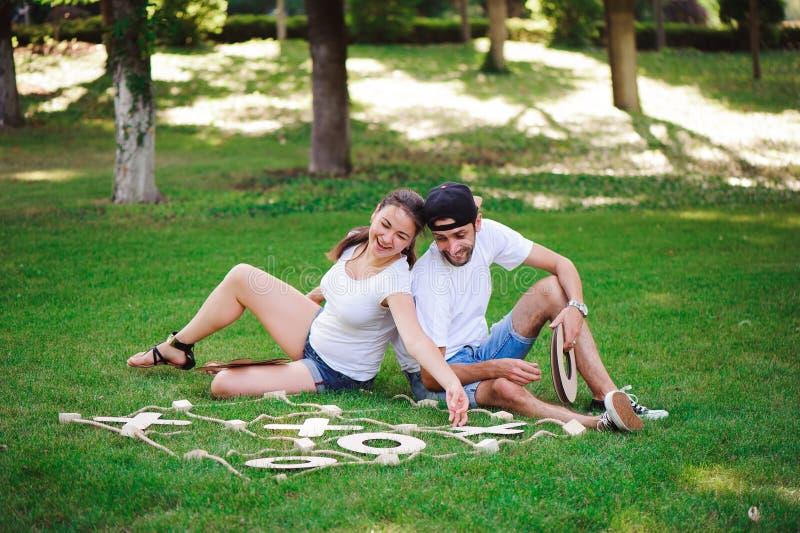 Lachende jongen en meisjes speel tic-TAC-teen in het park stock afbeeldingen